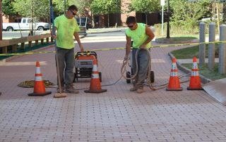 men working on red brick walkway